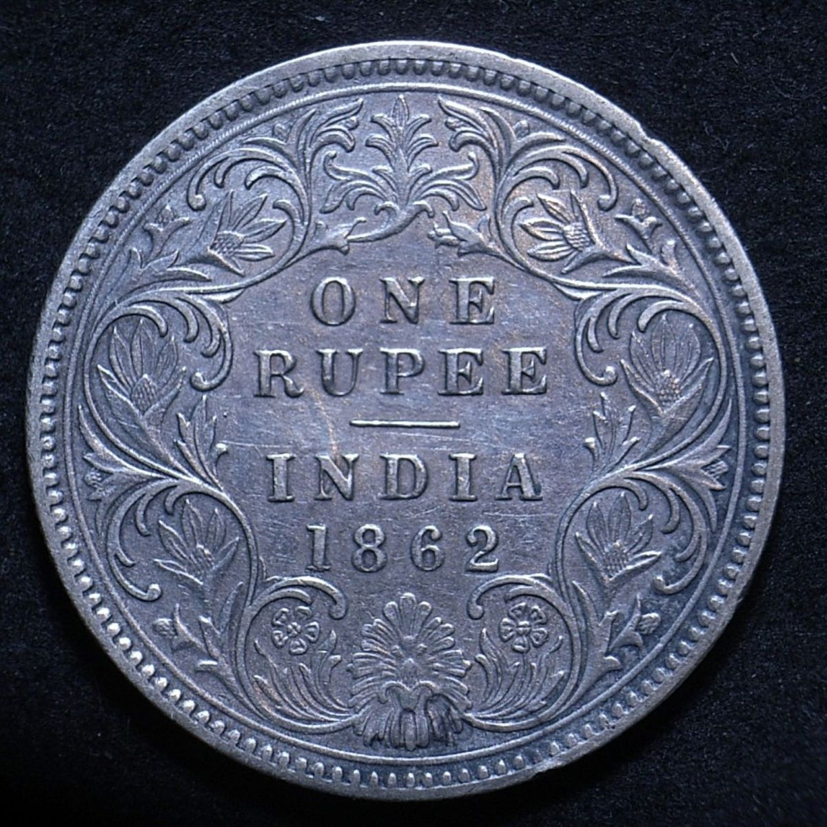 Close up of Indian 1862 rupee reverse showing the coin's detail